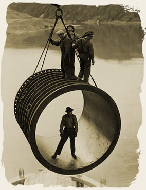Four men, three standing on top and one standing inside, riding on large casing section of pipe suspended by cable as it is moved into position by a crane, reservoir in the background during construction of the Grand Coulee Dam, Washington, 1936-46